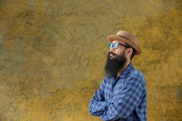 Jovem com uma barba longa, vestindo um chapéu e óculos Foto gratuita