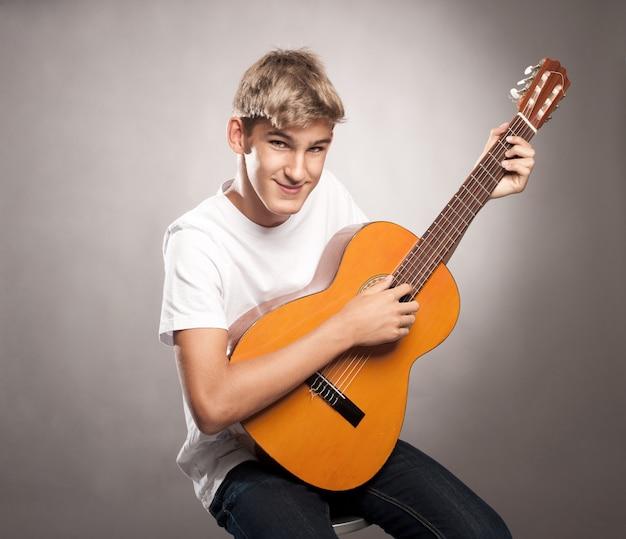 Jovem com violão em um fundo cinza Foto Premium
