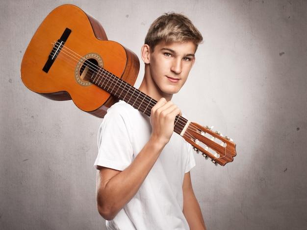 Jovem com violão na cinza Foto Premium