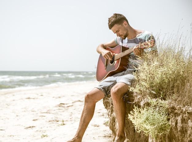 Jovem com violão na praia Foto gratuita