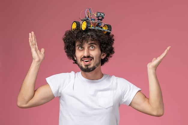 Jovem com visão frontal colocando sua inovação robótica na cabeça Foto gratuita