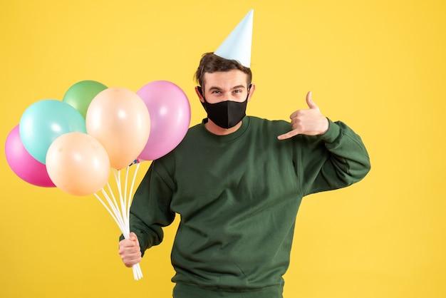Jovem com vista frontal com tampa de festa e balões coloridos fazendo sinal de me chame de pé no amarelo Foto gratuita