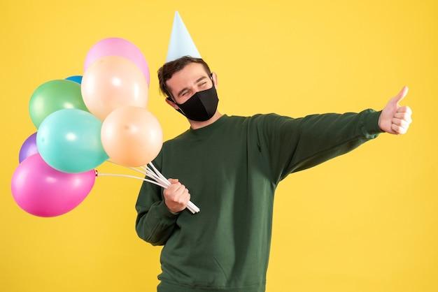 Jovem com vista frontal com tampa de festa e balões coloridos fazendo sinal de polegar para cima em amarelo Foto gratuita