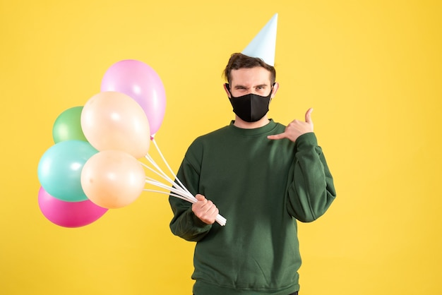 Jovem com vista frontal com tampa de festa e balões coloridos fazendo sinal de telefone em amarelo Foto gratuita
