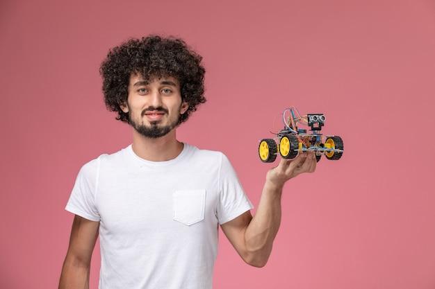 Jovem com vista frontal segurando seu robô eletrônico Foto gratuita