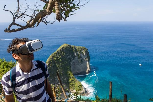 Jovem, com, vr, óculos, em, kelingking, praia, ligado, a, ilha, de, nusa, penida, em, indonésia Foto Premium