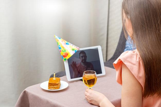 Jovem comemora aniversário durante a quarentena. festa de aniversário virtual on-line com sua amiga ou amante. chamada de vídeo no tablet. Foto Premium