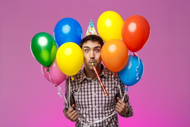 Jovem comemorando aniversário, segurando balões coloridos sobre parede roxa. Foto gratuita
