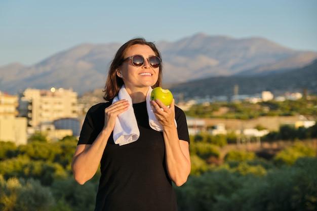 Jovem comendo uma maçã ao ar livre Foto Premium