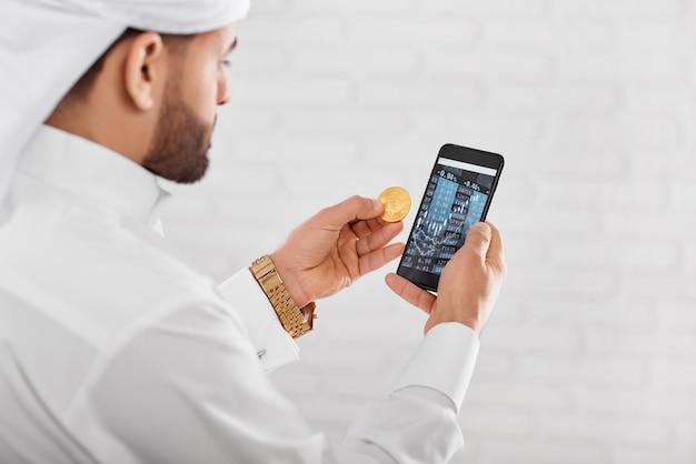 Jovem comerciante muçulmano detém bitcoin dourado e telefone celular Foto Premium