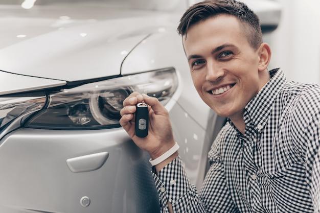 Jovem comprando carro novo na concessionária Foto Premium