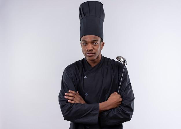Jovem confiante afro-americana com uniforme de chef cruza os braços e segura a concha isolada no fundo branco com espaço de cópia Foto gratuita