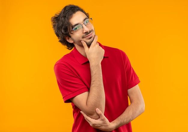 Jovem confiante de camisa vermelha com óculos ópticos coloca a mão no queixo isolado na parede laranja Foto gratuita