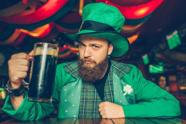 Jovem confiante e sério no terno verde do st. patrick sente-se à mesa no pub e pose. ele segura uma caneca de cerveja preta. Foto Premium