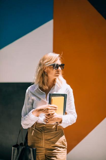 Jovem, confiante, executiva, segurando, diário, em, mão, ficar, contra, parede colorida Foto gratuita