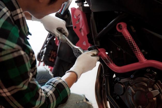 Jovem consertando uma motocicleta. Foto Premium