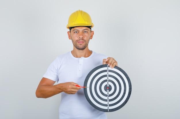 Jovem construtor em t-shirt branca, capacete de segurança segurando o alvo de dardos e a flecha de dardo, vista frontal. Foto gratuita