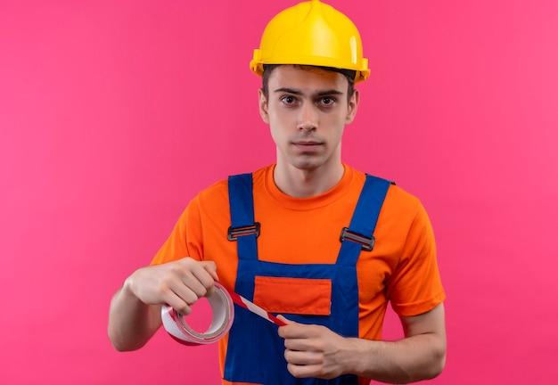 Jovem construtor usando uniforme de construção e capacete de segurança segura uma fita vermelha e branca de sinalização de alguém Foto gratuita