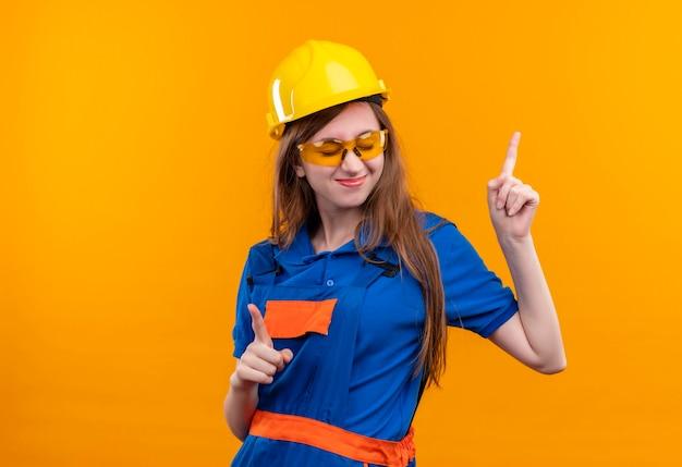 Jovem construtora com uniforme de construção e capacete de segurança se divertindo, sorrindo alegremente, apontando o dedo indicador para cima em pé sobre a parede laranja Foto gratuita
