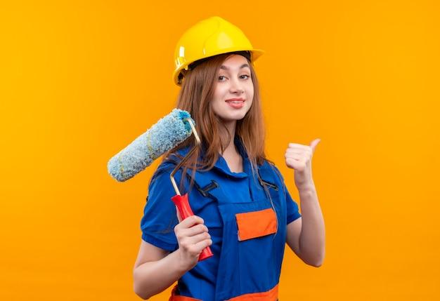 Jovem construtora com uniforme de construção e capacete de segurança segurando o rolo de pintura mostrando os polegares para cima sorrindo confiante em pé sobre a parede laranja Foto gratuita