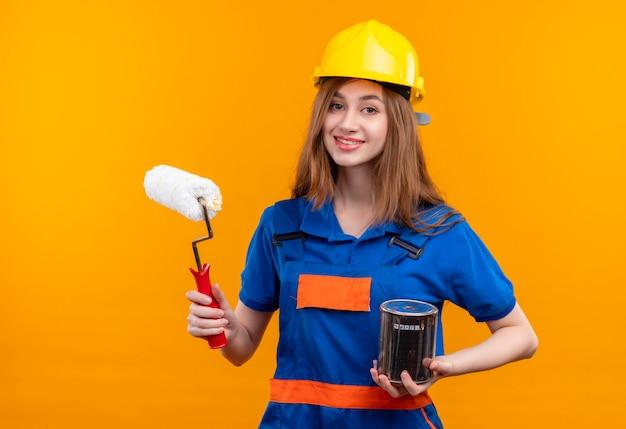Jovem construtora com uniforme de construção e capacete de segurança segurando uma lata de tinta e um rolo sorrindo Foto gratuita