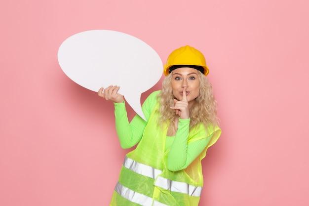 Jovem construtora de frente para o capacete com um terno de construção verde segurando uma placa branca de silêncio no espaço rosa Foto gratuita