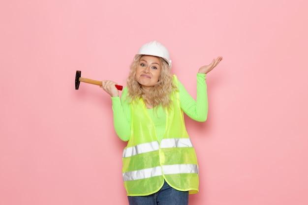 Jovem construtora em construção verde com capacete amarelo segurando um martelo no espaço rosa trabalho de arquitetura Foto gratuita