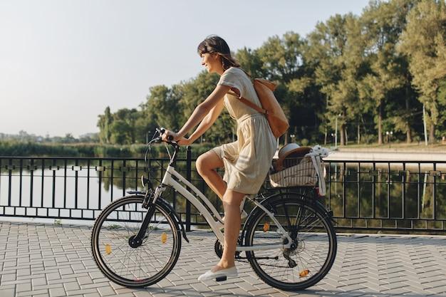 Jovem contra o fundo da natureza com bicicleta Foto gratuita