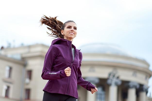 Jovem corredor feminino com capuz está correndo na rua da cidade Foto Premium