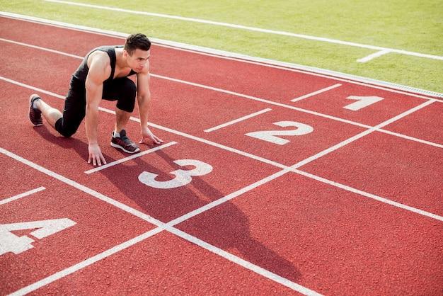 Jovem corredor masculino se preparando para começar a posição na pista de corrida Foto gratuita