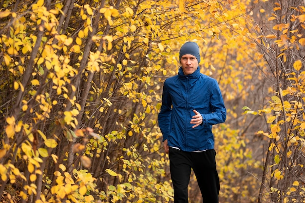 Jovem correndo na trilha na floresta Foto gratuita