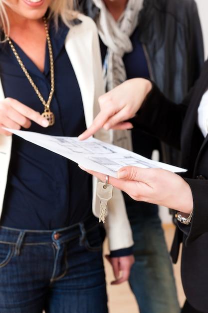 Jovem corretor de imóveis explica contrato de locação para casal Foto Premium