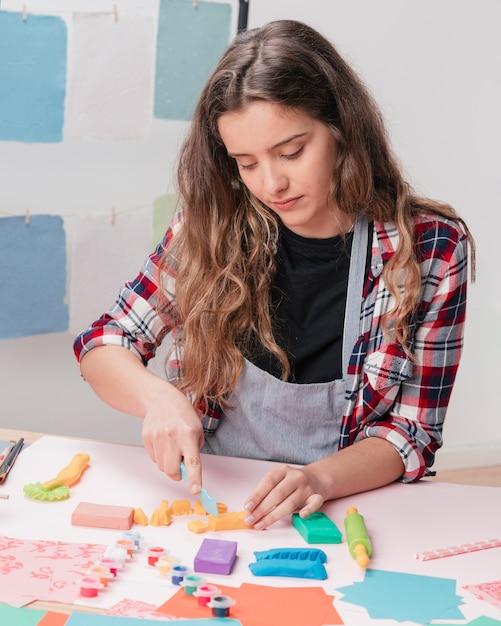 Jovem, corte, argila, usando, argila, cortador, escrivaninha Foto gratuita