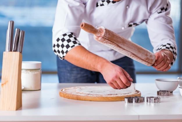 Jovem cozinhar biscoitos na cozinha Foto Premium