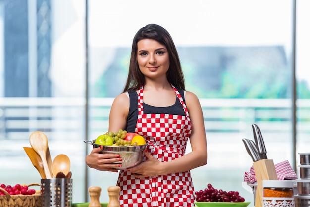 Jovem cozinhar com frutas na cozinha Foto Premium