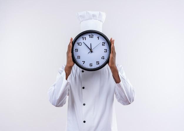 Jovem cozinheira afro-americana com uniforme de chef fecha rosto com relógio isolado no fundo branco com espaço de cópia Foto gratuita