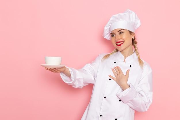 Jovem cozinheira de terno branco segurando uma xícara de café com um leve sorriso na cozinha do espaço rosa Foto gratuita