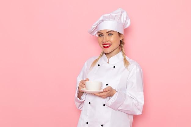 Jovem cozinheira de terno branco segurando uma xícara de café com um sorriso no cozinheiro espacial rosa Foto gratuita