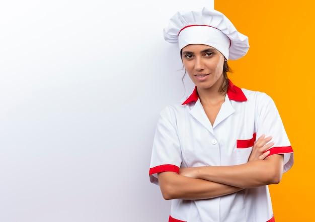 Jovem cozinheira satisfeita vestindo uniforme de chef em pé com parede branca e cruzando as mãos com espaço de cópia Foto gratuita