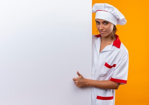 Jovem cozinheira satisfeita vestindo uniforme de chef, segurando uma parede branca com o polegar para cima com espaço de cópia Foto gratuita
