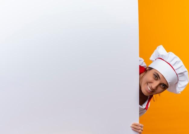 Jovem cozinheira sorridente usando uniforme de chef, segurando uma parede branca com espaço de cópia Foto gratuita