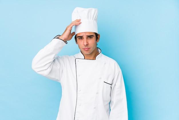 Jovem cozinheiro homem isolado sendo chocado, ela se lembrou de reunião importante. Foto Premium