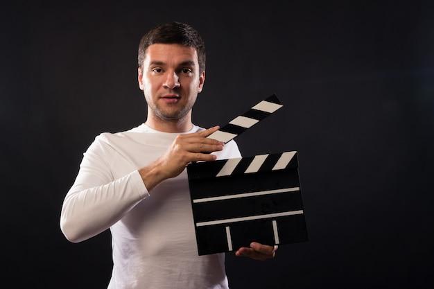 Jovem de aparência caucasiana está segurando uma claquete. Foto Premium