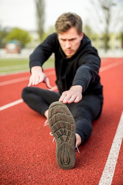 Jovem de aptidão sentado na pista de corrida, fazendo exercícios de alongamento Foto gratuita