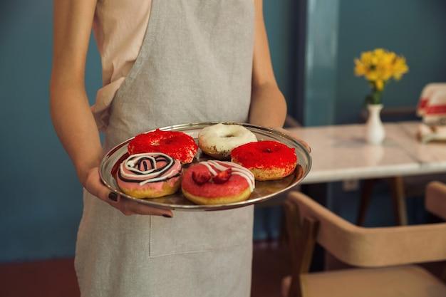 Jovem de avental segurando a bandeja com donuts Foto gratuita