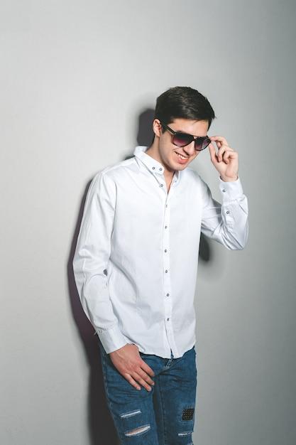 Jovem de bermuda e camisa branca está sorrindo em pé perto da parede com óculos Foto Premium