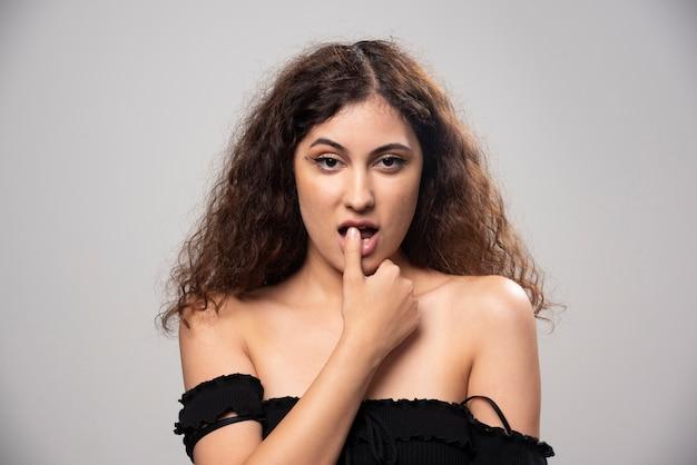 Jovem de blusa preta com cabelo encaracolado posando. foto de alta qualidade Foto gratuita
