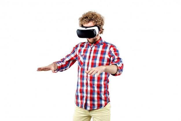 Jovem de cabelos cacheados na camisa xadrez, usando um fone de ouvido vr e exp Foto Premium
