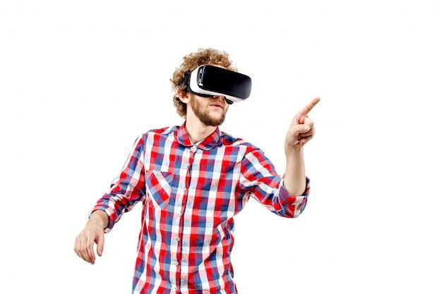 Jovem de cabelos cacheados na camisa xadrez, usando um fone de ouvido vr Foto Premium