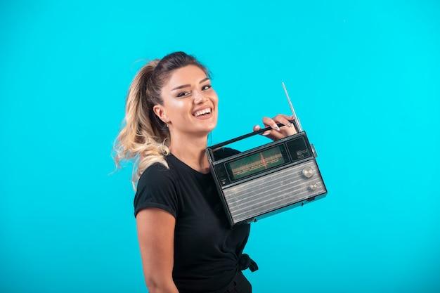 Jovem de camisa preta segurando um rádio vintage e se sente positiva. Foto gratuita